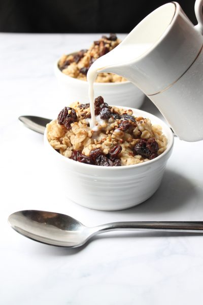 milk being poured over a small bowl of oatmeal with raisins