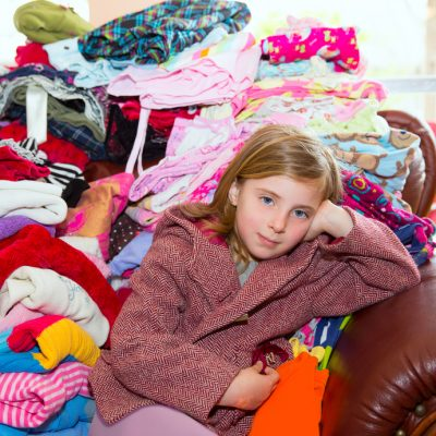 girl sitting on the couch surrounded by lots of clothes