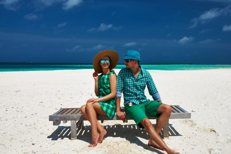 couple in green on a beach