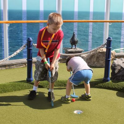 Kids playing mini golf on a cruise ship