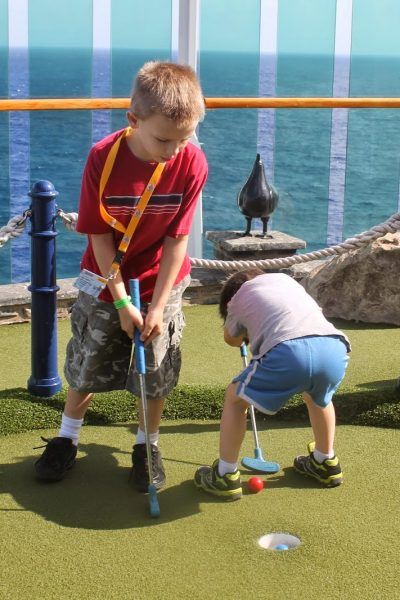 Kids playing mini golf on a cruise ship